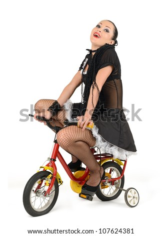 Beautiful french maid, at the children's bicycle on white background - stock photo