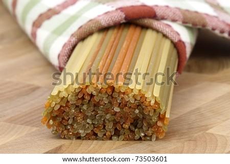 beautiful fresh and raw spaghetti on fine wood kitchen station shallow DOF - stock photo