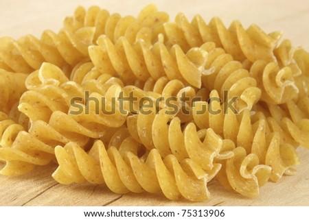 beautiful  fresh and raw wholegrain fusilli ,thick, corkscrew shaped pasta on wood board.  shallow DOF - stock photo