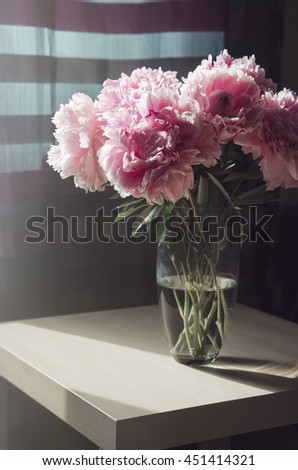 Beautiful fresh bouquet of pink peonies roses flowers in glass vase on the table with sunlight background. Summer time concept. Still life, rustic style. Fresh floral, home decor. Text, copy space - stock photo