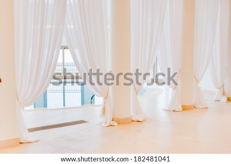beautiful fresh clean floor length white drapes fastened to pillars in front of light airy windows surrounding an indoor swimming pool at a health resort or spa - stock photo