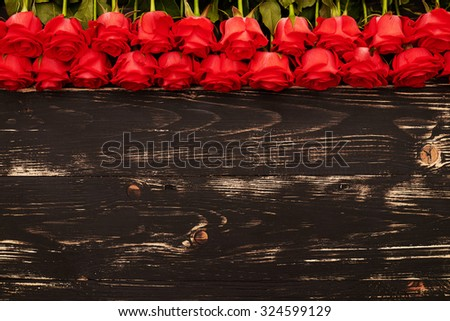 beautiful fresh roses over wooden background with empty copyspace for your text - stock photo