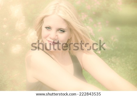beautiful fresh woman in nature with roses at her side and looking straight into the camera - stock photo