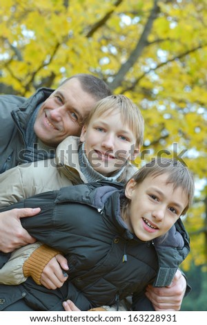 Beautiful friendly family for a walk in the park in autumn - stock photo