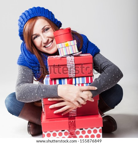 Beautiful friendly redhead woman sitting cross legged on the floor hugging a tall stack of colorful decorative Christmas gifts and peering round the side to smile at the camera - stock photo