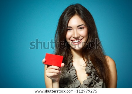 beautiful friendly smiling confident girl showing red card in hand, over blue background - stock photo