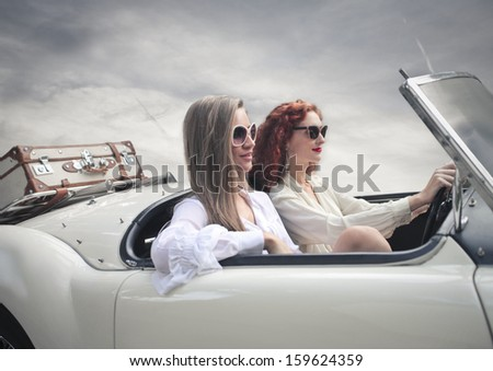 beautiful friends traveling on a vintage car - stock photo