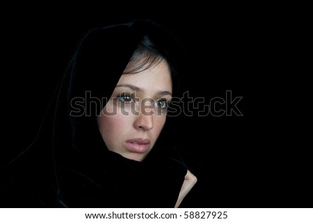 Beautiful frightened woman wrapped in a scarf on a black background. - stock photo