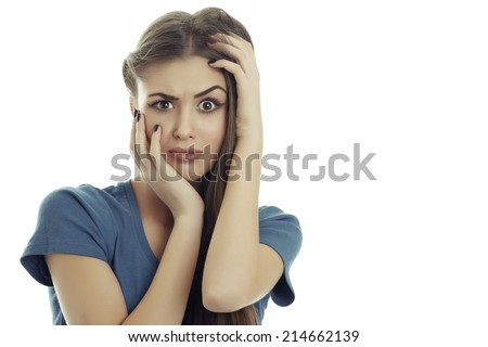 Beautiful frowning young woman with hands on her head in a surprise, despair, embarrassment or panic gesture against white background. What have I done!? - stock photo
