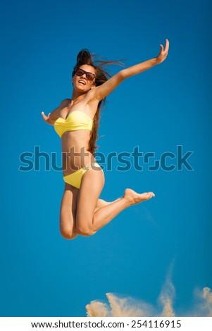 beautiful fun and joy brunette lady smiling woman in yellow bikini jump  blue sky  has sports and tan body - stock photo