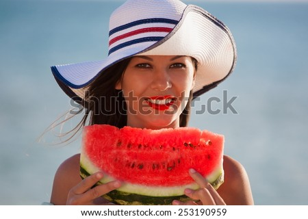 beautiful fun and joy brunette lady woman in white hat eating red juicy watermelon in blue sea water background have smiling lips and tan skin - stock photo