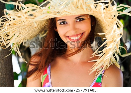 beautiful fun and joy brunette smiling woman in multicolor bikini and big hat - stock photo