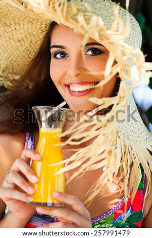 beautiful fun and joy brunette smiling woman in multicolor bikini and sun hat drink orange mango cocktail in tropical forest - stock photo