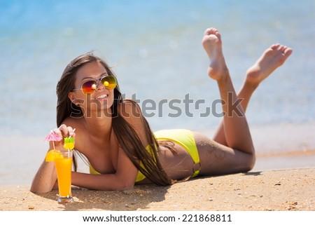 beautiful fun and joy brunette smiling woman in yellow bikini drink orange cocktail in  tropical  blue sea water bali has sports and tan body - stock photo
