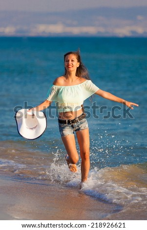 beautiful fun and joy brunette woman in jeans shorts run  blue sea water has sports and tan body - stock photo