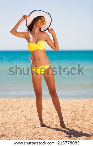 beautiful fun and joy brunette woman in yellow bikini posing  tropical  blue sea water has sports and tan body