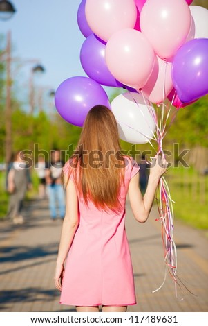 Beautiful fun back woman holding multicolored helium balloons. Has smiling face, long hair, clothed pink dress. Has slim body. Portrait in city park. Sunny day and blue sky. Close up - stock photo