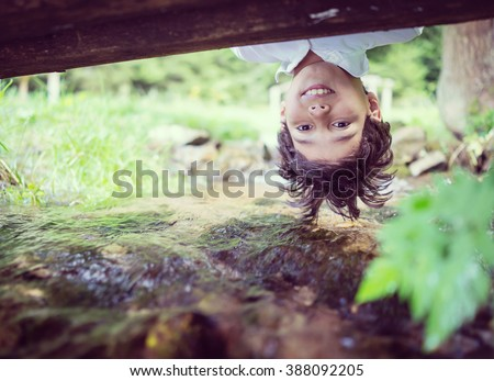 Beautiful fun day for upside down cute little boy on mountain creek in nature