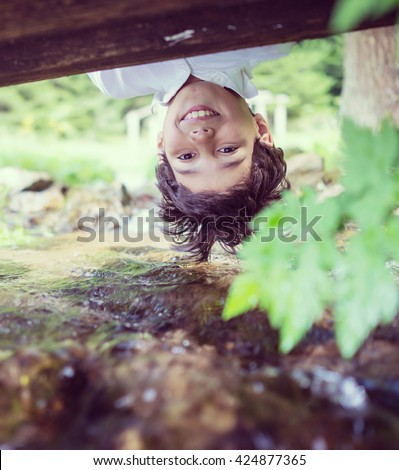 Beautiful fun day for upside down cute little boy on mountain creek in nature - stock photo