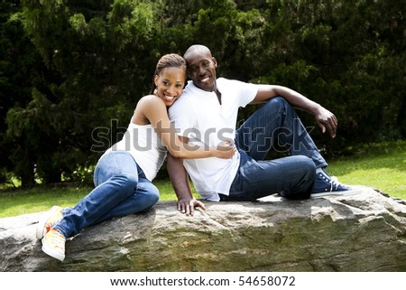 Beautiful fun happy smiling African American couple in love wearing white shirts and blue jeans, sitting on a rock in a park, woman hugging guy. - stock photo