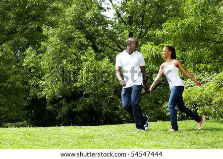 Beautiful fun happy smiling African American young couple running playing in park, wearing white shirts and blue jeans. - stock photo