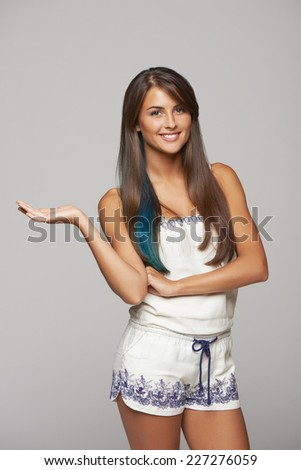 Beautiful funky woman with blue hair coloring showing holding on the palm blank copy space, looking at camera, over gray background - stock photo