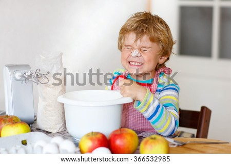 beautiful funny blond little kid boy baking apple cake and muffins in domestic kitchen happy