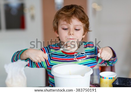 Beautiful funny blond little kid boy baking cake and tasting dough in domestic kitchen. Happy child having fun with working with mixer, flour, eggs and fruits at home. - stock photo