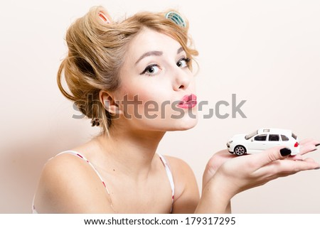 beautiful funny blond pinup woman with green eyes & curlers playing with car in the hands portrait - stock photo