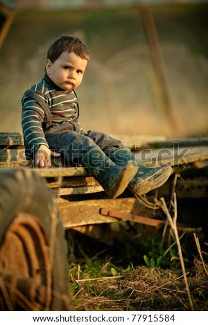 beautiful funny boy sitting on cart - stock photo