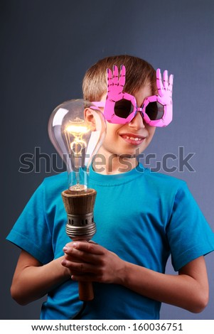 Beautiful funny child in stylish sunglasses holding a big vintage light bulb illuminating the darkness. Creative education concept. - stock photo