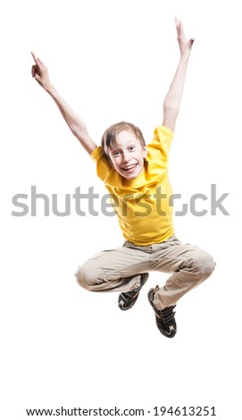 Beautiful funny child in yellow t-shirt jumping in excitement and laughing over white background - stock photo