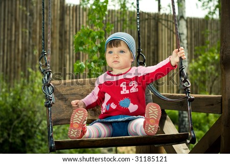 beautiful funny child on the swings - stock photo