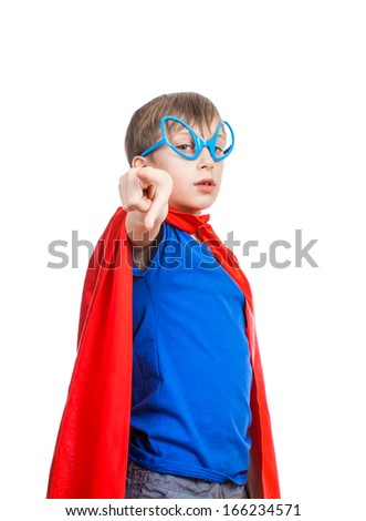 Beautiful funny child pretending to be superhero standing, looking strong and powerful, pointing his index finger to the camera - stock photo