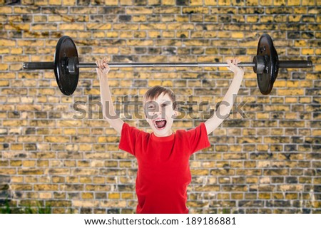 Beautiful funny child superhero holding very big weight screaming (fitness concept) - stock photo