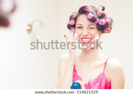 Beautiful funny girl applying shaving foam to her face happy smiling & looking at camera - stock photo