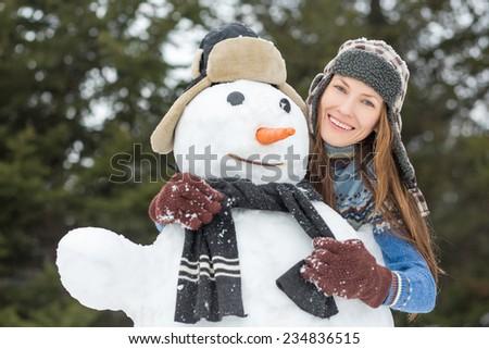 Beautiful funny winter woman near snowman - stock photo