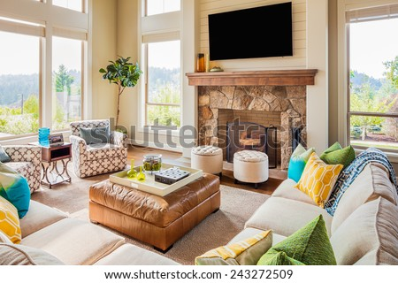 Beautiful Furnished Living Room Interior in New Luxury Home with Fireplace, Couches, Chairs, and Television - stock photo
