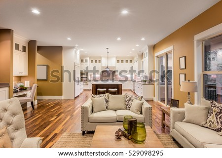 Beautiful Furnished Living Room With Hardwood Floors And Kitchen View In  New Luxury Home. Kitchen