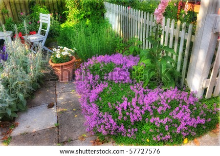 Beautiful garden at sunset - flowers and furniture - stock photo