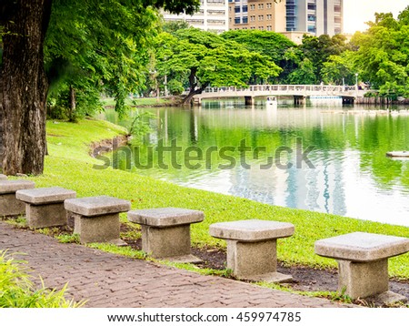 Beautiful garden park from green tree, pavement and stone chair near river side, white bridge cross pond which reflection water