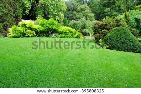 Beautiful Garden with a Freshly Mowed Lawn - stock photo