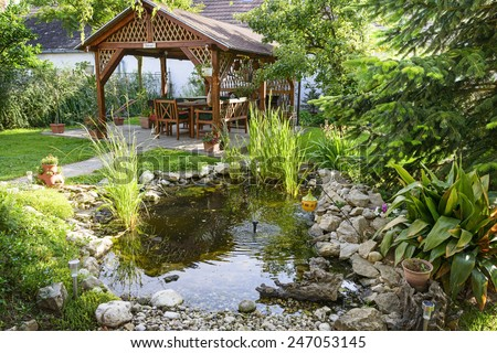 Beautiful Garden With Bench And Little Pond To Relax - stock photo
