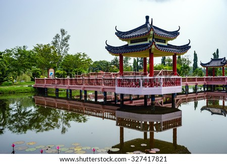 Beautiful garden with Chinese architectural bridge and reflection in the lake - stock photo