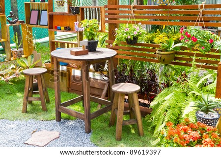 beautiful garden with flower and wooden table and chairs - home decoration - stock photo