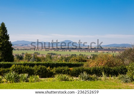 Beautiful garden with green trees and blue sky above the distant countryside - stock photo