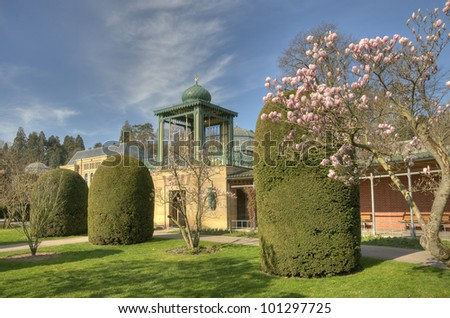 Beautiful Garden with Magnolia and moorish Building - stock photo