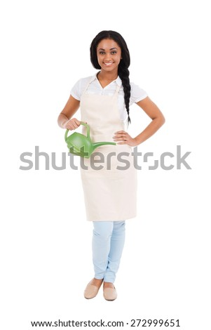 Beautiful gardener. Full length of beautiful young African woman in apron carrying watering can and smiling while standing against white  - stock photo