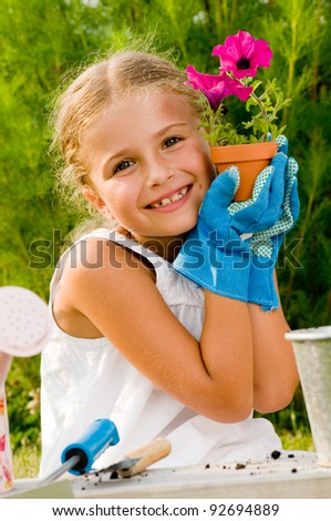 Beautiful gardener - little gardener girl with the flower planted into the flowerpot - stock photo