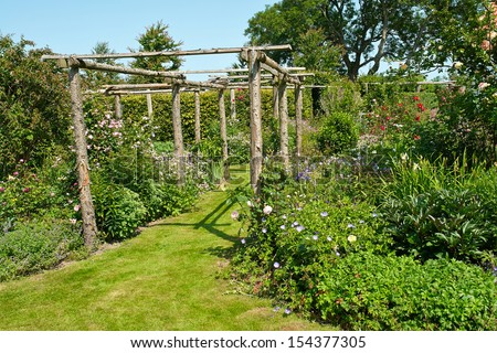 Beautiful gardening project - creative garden tunnel archway in a classical garden - stock photo